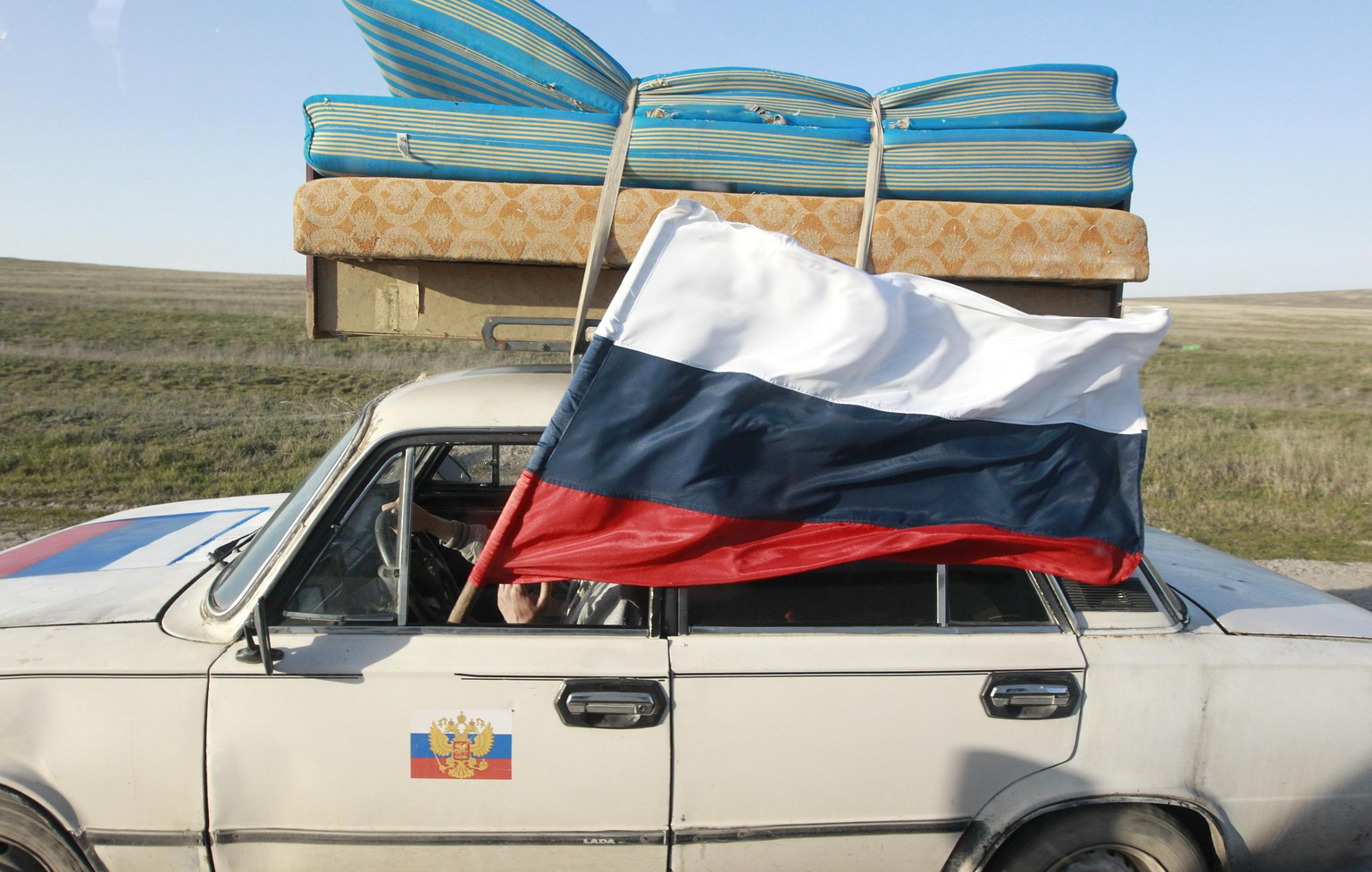 A car drives with a Russian flag on a road outside the Crimean port city of Feodosia in this March 24, 2014 file photo. Six years after losing land in a war with Russia, Georgians believe the struggle for Ukraine will decide their own fate, and hope NATO and the European Union will now speed up their integration into the Western fold. Picture taken March 24, 2014. To match Analysis story UKRAINE-CRISIS/GEORGIA REUTERS/Shamil Zhumatov/Files (UKRAINE - Tags: POLITICS MILITARY)