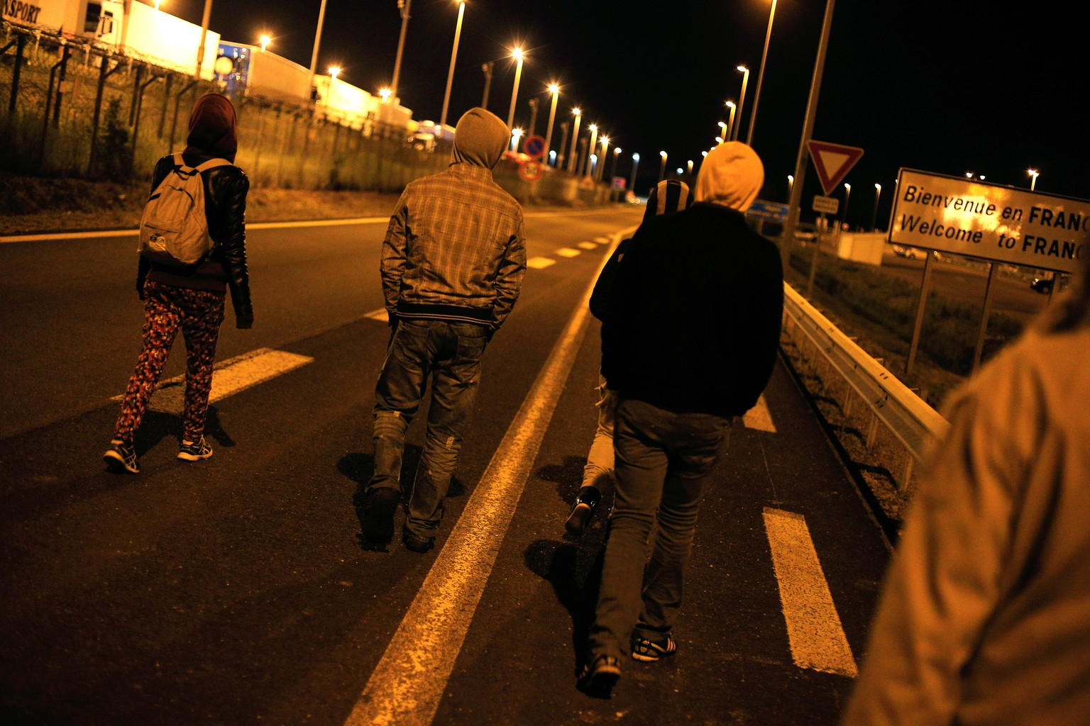 Migrants walk on a road outside the Eurotunnel area, in Calais, northern France, Wednesday, July 29, 2015. About 2,100 migrants tried to storm the area surrounding the Eurotunnel early Tuesday before being repelled by police, an official in the northern French port of Calais said. (AP Photo/Thibault Camus)