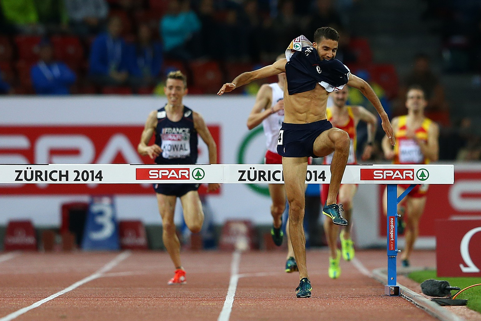 ZURICH, SWITZERLAND - AUGUST 14:  Mahiedine Mekhissi-Benabbad of France takes his vest off as he clears the last jump on his approach to the finish line to claim gold in the Men's 3000 metres Steeplechase final during day three of the 22nd European Athletics Championships at Stadium Letzigrund on August 14, 2014 in Zurich, Switzerland.  (Photo by Michael Steele/Getty Images)