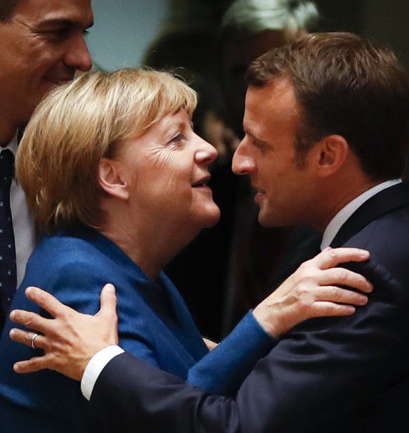German Chancellor Angela Merkel, left, is greeted by French President Emmanuel Macron during a round table meeting at an EU summit in Brussels, Wednesday, Oct. 17, 2018. European Union leaders are converging on Brussels for what had been billed as a