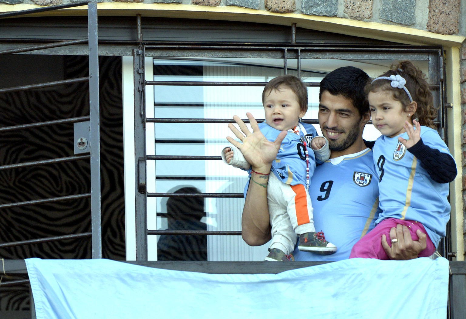 Uruguay's soccer player Luis Suarez, center, with his children Benjamin, left, and Delfina, waves to fans from his home, before the start of his team's World Cup round 16 match with Colombia, on the outskirts of Montevideo, Uruguay, Saturday, June 28, 2014. FIFA banned Suarez from all football activities for four months for biting an opponent at the World Cup, a punishment that rules him out of the rest of the tournament. (AP Photo/Matilde Campodonico)