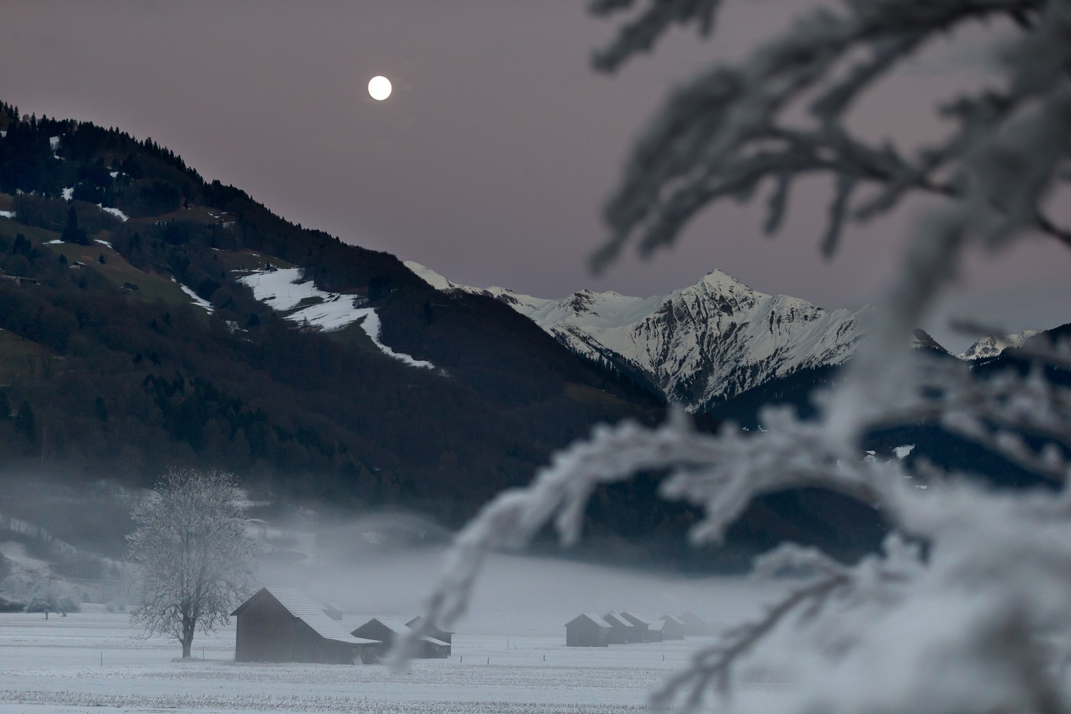Der Mond erhellt die nebelverhangene Ebene in den Schwellenen in Gruesch im Vorderpraettigau, am Sonntag, 15. Dezember 2013. (KEYSTONE/Arno Balzarini) 