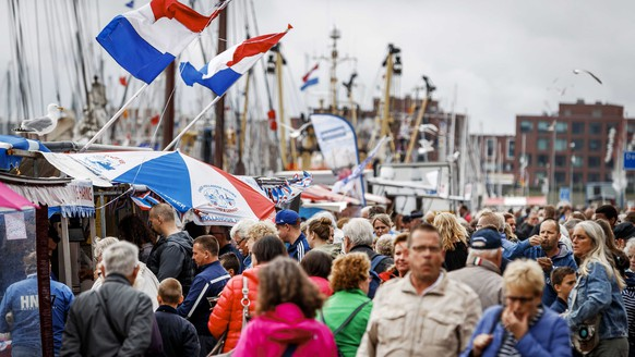 epa05374485 Visitors walk during Vlaggetjesdag (Flagday), the day on which traditionally the new herring is shipped into the harbor of Scheveningen, The Netherlands, 18 June 2016. The event it's been a trademark for over sixty years in this subdistrict of The Hague.  EPA/REMKO DE WAAL