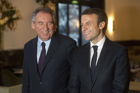 French centrist politician Francois Bayrou, left, and candidate for the 2017 French presidential election, Emmanuel Macron, pose for photographers after a meeting, in Paris, Thursday, Feb. 23, 2017. Once-prominent centrist Bayrou shocked political observers by throwing his weight behind presidential candidate Emmanuel Macron with whom he said he wanted to form