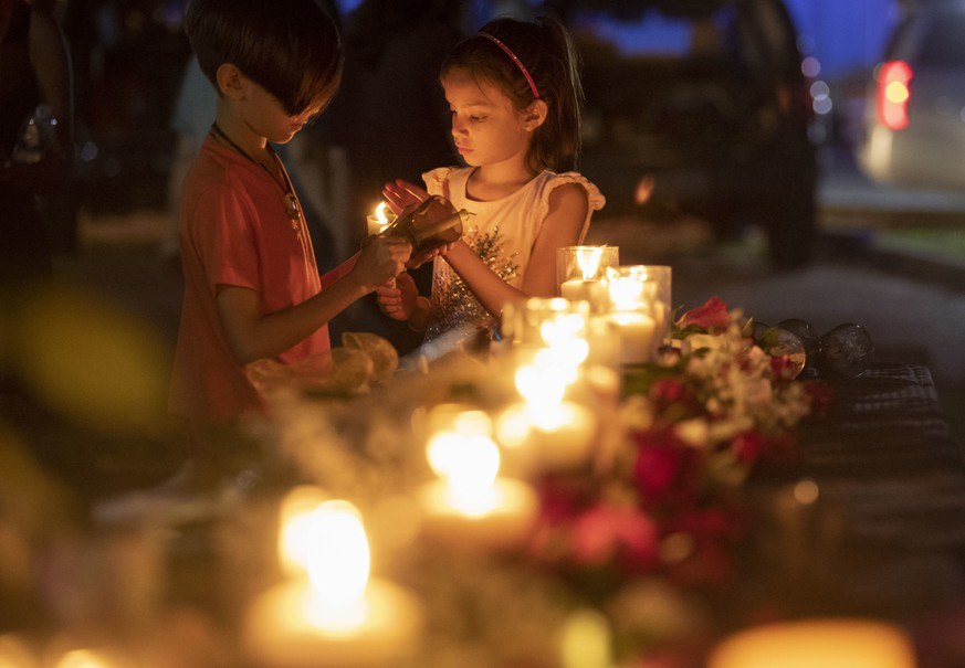 Lucrecia Martinez, 7, and her brother Luciano, 9, of Dickinson light candles during a vigil held in the wake of a deadly school shooting with multiple fatalities at Santa Fe High School on Friday, May 18, 2018, in Santa Fe, Texas. (Stuart Villanueva/The Galveston County Daily News via AP)