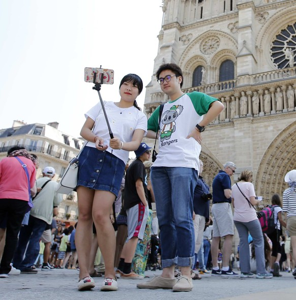 Tourists take a selfie in front of the Notre Dame Cathedral during a sunny morning in Paris, France, June 11, 2015. France, the world's top tourism draw, on Thursday announced a scheme to lure in even more tourists with a new fund intended to boost everything from hotels to its wine heritage and urged the French to be more welcoming. REUTERS/Charles Platiau