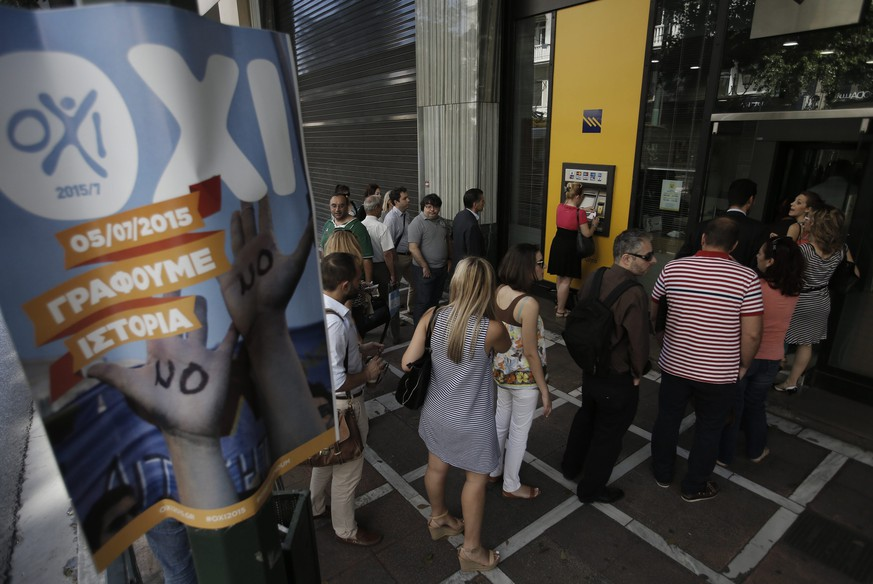 epa04827622 People queue to withdraw money from an ATM next to a poster supporting the No vote outside of a bank branch in Athens, Greece, 2 July 2015. Greek Prime Minister Tsipras remained steadfast in his controversial plan to hold a referendum on the bailout demands of creditors, as eurozone finance ministers discussed a request from Athens for new financial aid. During the televized address to the nation on 01 July 2015 Tsipras said that anyone equating a no-vote with a return to the drachma is 'telling lies,' and repeated his call for people to vote against the measures.  EPA/YANNIS KOLESIDIS
