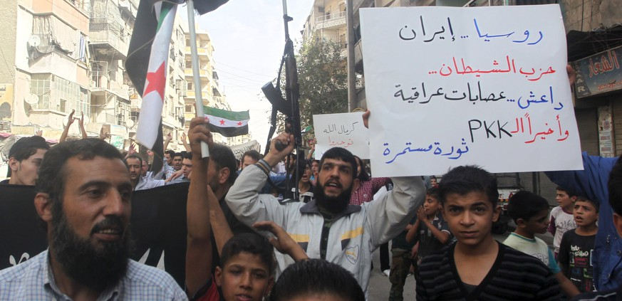 Residents carrying Free Syria Army flags and a weapon chant slogans as they protest against Russian airstrikes in Syria, in Aleppo, Syria October 2, 2015. Placard reads in Arabic,