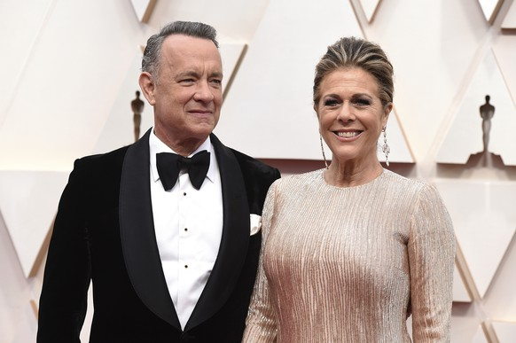 "FILE - In this Feb. 9, 2020 file photo, Tom Hanks, left, and Rita Wilson arrive at the Oscars at the Dolby Theatre in Los Angeles. The couple have tested positive for the coronavirus, the actor said in a statement Wednesday, March 11. The 63-year-old actor said they will be ""tested, observed and isolated for as long as public health and safety requires."" (Photo by Jordan Strauss/Invision/AP, File) Tom Hanks,Rita Wilson"