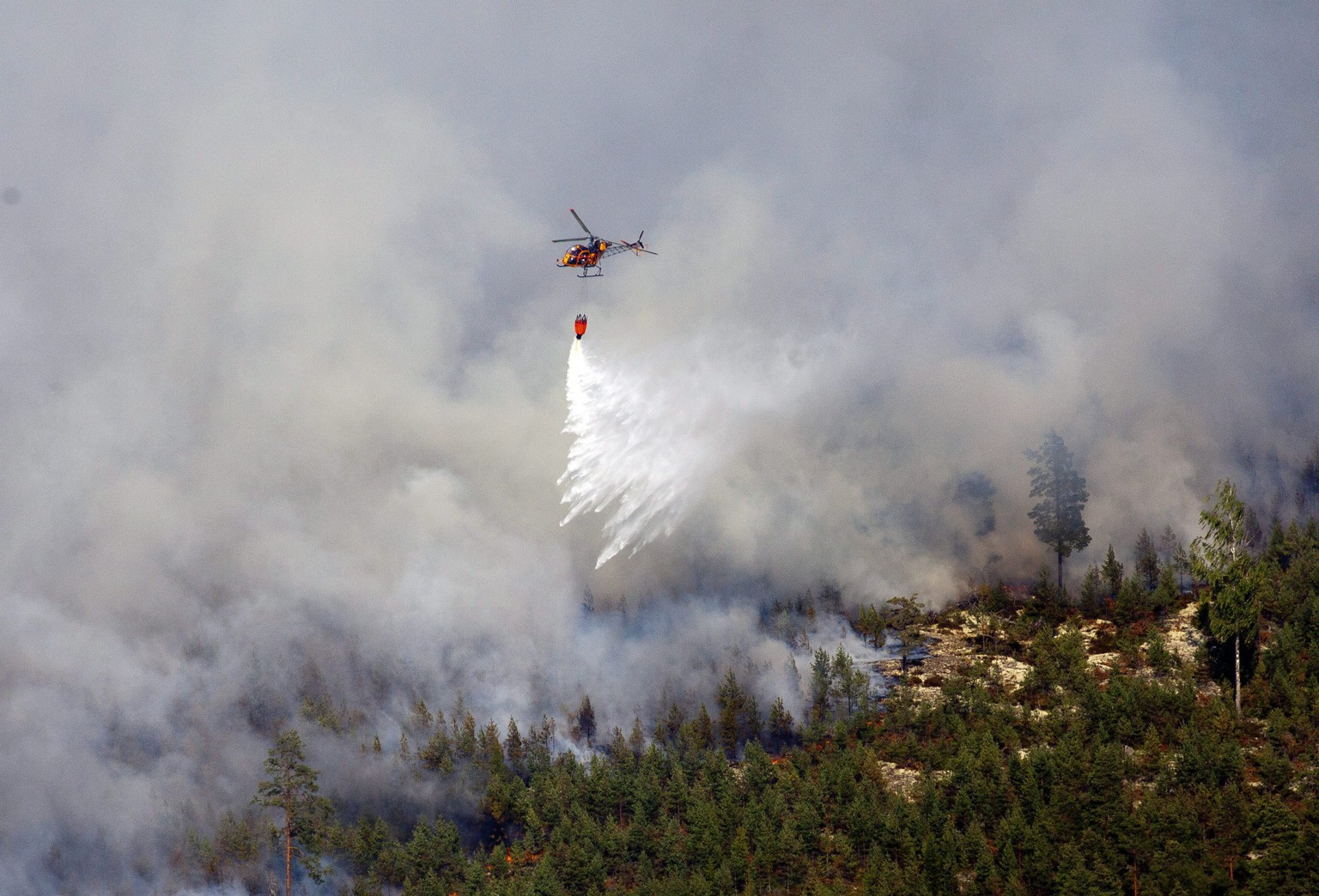 epa04340805 A photograph made available on 04 August 2014 shows a helicopter dumping water on the wildfire in the village of Rorbo near Sala, Sweden, 03 August 2014. The fire, covering thousands of hectares, is in its fifth day and firefighters believe it will burn for weeks or even months. It is classified as the worst forest fire in Sweden's modern history.  EPA/JOCKE BERGLUND SWEDEN OUT