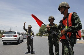 Thai soldiers direct traffic on a highway in Thailand's Ayutthaya province, May 21, 2014. Thailand's army chief summoned leaders of rival political groups and parties, Election Commission members and senators to a meeting on Wednesday, a day after he declared martial law, to discuss a way out of the country's political turmoil. REUTERS/Chaiwat Subprasom (THAILAND - Tags: CIVIL UNREST POLITICS MILITARY)