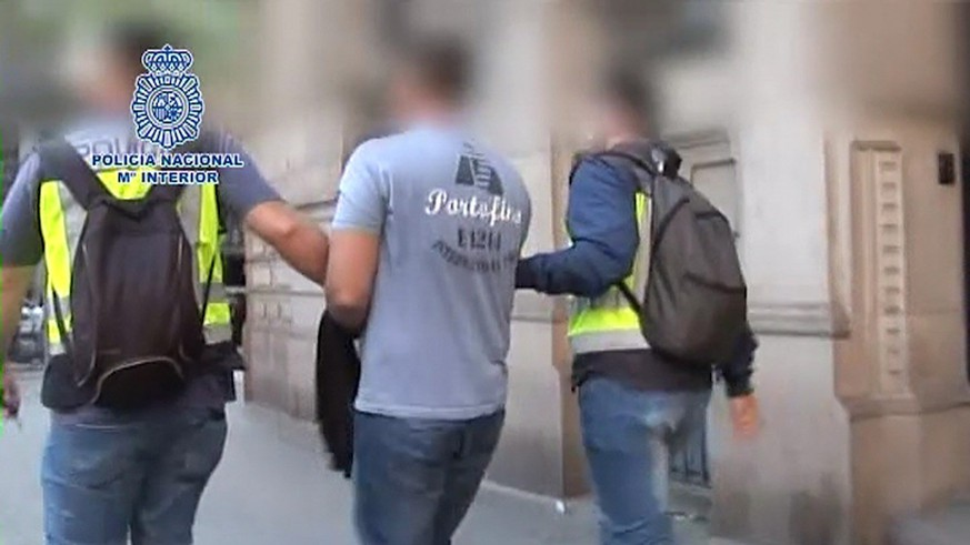 epa05902959 An undated handout photo made available by the Spanish National Police on 11 April 20117 shows two policemen escorting Russian programmer Pyotr Levashov (C) after his arrest in Barcelona, northeastern Spain. According to investigation sources, Levashov is one of the most wanted hackers for allegedly infecting computers with malware and asking a 'ransom' for releasing them. Levashov was arrested after US authorities issued an International Arrest Order against him.  EPA/SPANISH NATIONAL POLICE HANDOUT PIXELATED BY SOURCE HANDOUT EDITORIAL USE ONLY/NO SALES