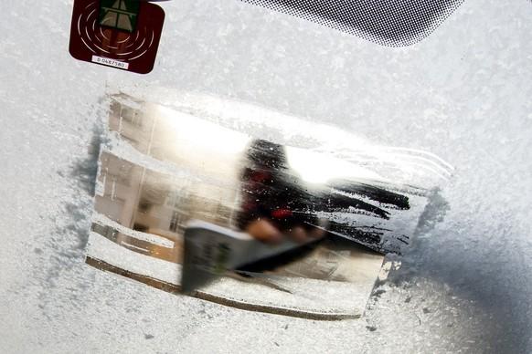 Человек снимает свою машину на лобовом стекле в Женеве, Швейцария, в понедельник, 22 декабря 2014 года. (ТРАПЕЦИЯ / Salvatore Di Nolfi)