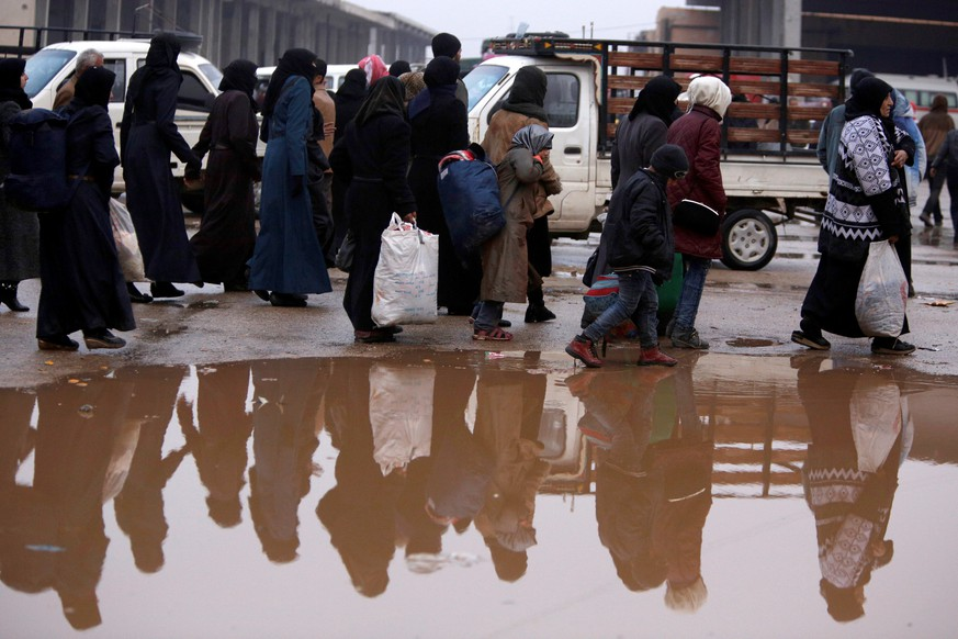 Syrians evacuated from eastern Aleppo walk with their belongings near a puddle of water in government controlled Jibreen area in Aleppo, Syria November 30, 2016. REUTERS/Omar Sanadiki