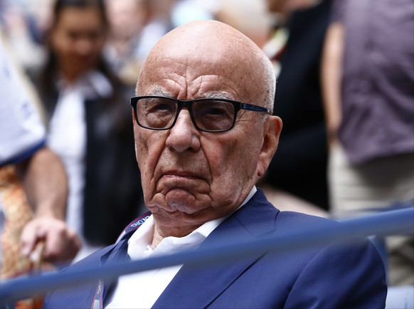 FILE- In this Sunday, Sept. 10, 2017 file photo, Rupert Murdoch waits for the start of the men's singles final of the U.S. Open tennis tournament in New York. Rupert Murdoch's British newspaper company has agreed to pay damages to a former intelligence officer whose computer was hacked by detectives working for Murdoch's now-defunct News of the World tabloid, lawyers said Friday, Oct. 6, 2017.  (AP Photo/Julio Cortez, File)