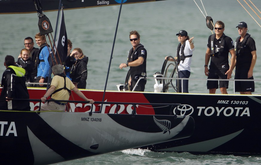 Catherine (3rd R), the Duchess of Cambridge, gestures as she steers an America's Cup yacht towards her husband, Britain's Prince William, after she crossed the finish line ahead of him while sailing on Auckland Harbour April 11, 2014. Britain's Prince William and his wife Kate are undertaking a 19-day official visit to New Zealand and Australia with their son George.   REUTERS/Phil Noble  (NEW ZEALAND - Tags: ROYALS)
