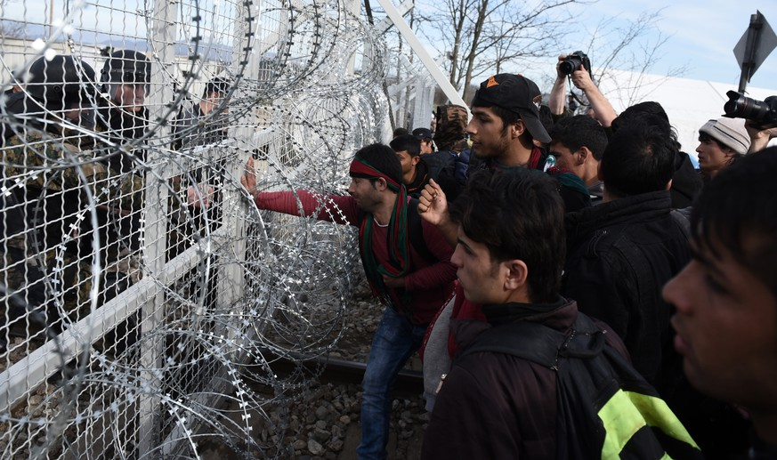 Afghan refugees push a fence at the Greek-Macedonia borderline as they try to enter Macedonia near the northern Greek village of Idomeni, Monday, Feb. 22, 2016. Greece's government warned Monday it expected a growing number of stranded migrants and asylum seekers after neighbor Macedonia further restricted border access at the weekend. (AP Photo/Giannis Papanikos)