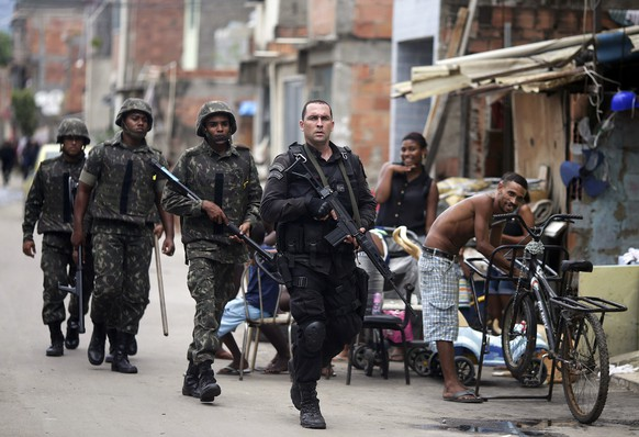 A policeman escorts Brazilian Army soldiers during an operation in the Mare slums complex in Rio de Janeiro March 26, 2014. Brazil will deploy federal troops to Rio de Janeiro to help quell a surge in violent crime following attacks by drug traffickers on police posts in three slums on the north side of the city, government officials said on Friday.