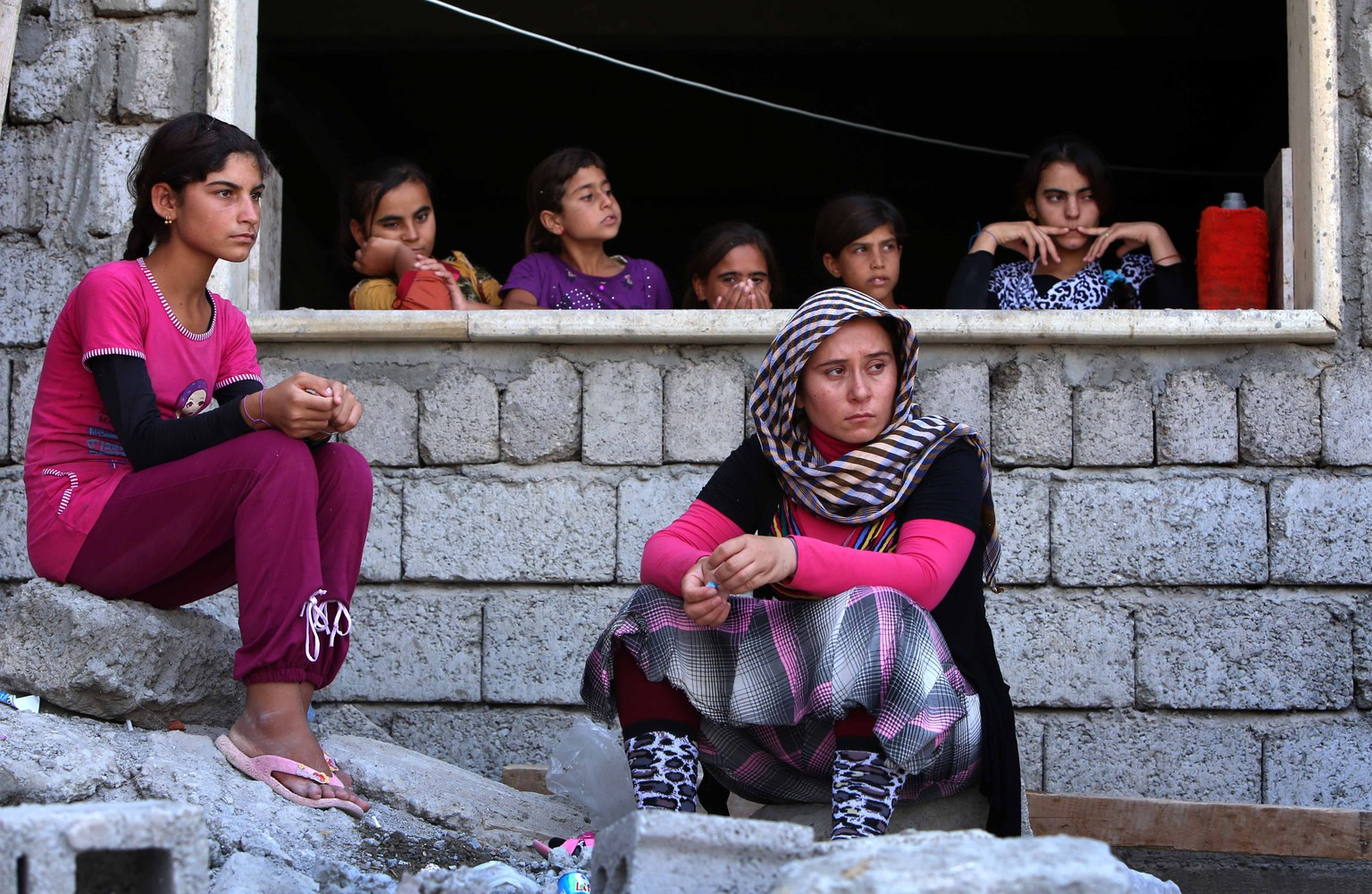 Iraqi Yazidi women who fled the violence in the northern Iraqi town of Sinjar, sit at a school where they are taking shelter in the Kurdish city of Dohuk in Iraq's autonomous Kurdistan region, on August 5, 2014. Islamic State (IS) Sunni jihadists ousted the Peshmerga troops of Iraq's Kurdish government from the northern Iraqi town of Sinjar, forcing thousands of people from their homes. The Yazidis, are a small community that follows a 4,000-year-old faith and have been repeatedly targeted by jihadists who call them