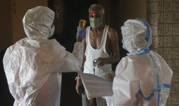 Health workers screen people for COVID-19 symptoms at a residential building in Dharavi , one of Asia's biggest slums, in Mumbai, India, Friday, Aug. 7, 2020. As India hit another grim milestone in the coronavirus pandemic on Friday, crossing 2 million cases and more than 41,000 deaths, community health volunteers went on strike complaining they were ill-equipped to respond to the wave of infection in rural areas.(AP Photo/Rafiq Maqbool)