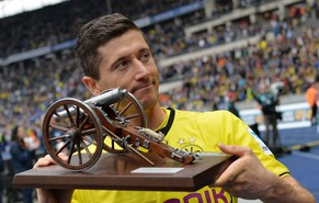 Dortmund's Polish striker Robert Lewandowski holds his trophy after he was awarded top scorer of the German Bundesliga first division following the German first division Bundesliga football match Hertha BSC Berlin vs Borussia Dortmund in Berlin on May 10, 2014. Dortmund won the match 0-4, with Lewandowski scoring two of the goals.    AFP PHOTO / OLIVER LANG