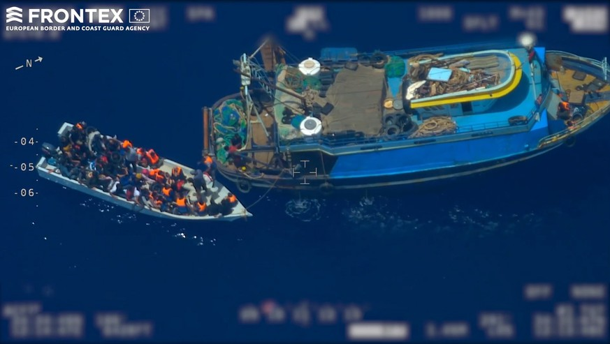 epa07669905 A screen grab taken from an undated handout video made available by the European Border and Coast Guard Agency (Frontex) on 24 June 2019 shows migrants coming out of from a fishing trawler (R) to board a wooden boat (L), at high seas in the Mediterranean. According to Frontex, some 80 people emerged from below the deck of the fishing trawler -- a so-called 'mother boat' that people smugglers use to carry large groups of migrants across the sea -- and got into the smaller boat. After the migrant boat was filled with people it slowly headed toward the Italian island of Lampedusa as the fishing trawler quickly moved away. Frontex said that it used a plane and a drone to observe the fishing trawler and the boat with migrants for several hours; it also alerted Italian and Maltese authorities and the EUNAVFOR Med (Operation Sophia). Italian authorities, who are investigating the case, started a complex operation that caught up with the bigger vessel and arrested the suspected people smugglers and the migrant boat was intercepted in the Italian waters.  EPA/FRONTEX, THE EUROPEAN BORDER AND COAST GUARD AGENCY HANDOUT  HANDOUT EDITORIAL USE ONLY/NO SALES