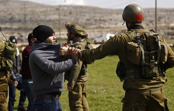 A Palestinian protester scuffles with an Israeli soldier during a protest against what Palestinians say is land confiscation for Jewish settlements, in the West Bank village of Silwad near Ramallah February 9, 2015. 
