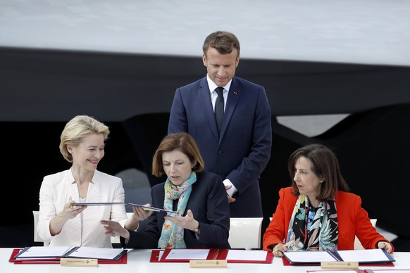 French President Emmanuel Macron, watches German Defense Minister Ursula von der Leyen, left, French Defense Minister Florence Parly and Spanish Defense Minister Margarita Robles, right, during a signature ceremony as part as the unveiling of the French-German-Spanish new generation fighter model during Le Bourget Airport near Paris, France, Monday June 17, 2019. (Yoan Valat/Pool via AP)