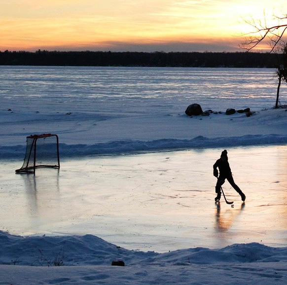 A youth plays pond hockey as the sun rises on Pigeon Lake in the region of Kawartha Lakes Ontario February 4, 2015. Hockey-mad Canadians are looking forward to one of the year's most anticipated televised events, CBC's
