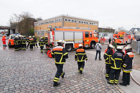 epa04704511 Firemen stand in front of residential containers for refugees in Hamburg, Germany, 14 April 2015. A fire started in one of the containers on the compound. Reportedly all 15 residents are not injured.  EPA/DANIEL BOCKWOLDT