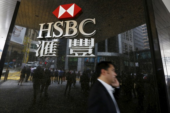 A man walks past a logo of HSBC outside a branch at the financial Central district in Hong Kong, China June 2, 2015. HSBC Holdings Plc could announce thousands of job cuts at a strategy day next week, Sky News reported on Monday, part of chief executive Stuart Gulliver's overhaul plan that could also see him sell operations in Brazil and Turkey and take a knife to his investment bank.      REUTERS/Bobby Yip