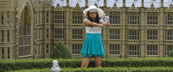 A woman poses for a selfie in front of a miniature replica of London's Houses of Parliament, at a theme park called