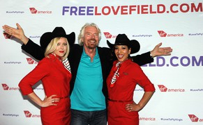 In this Monday, May 5, 2014 photo released by Virgin America Airlines, Virgin Group Founder Sir Richard Branson, center, is joined by Virgin America teammates during an informal