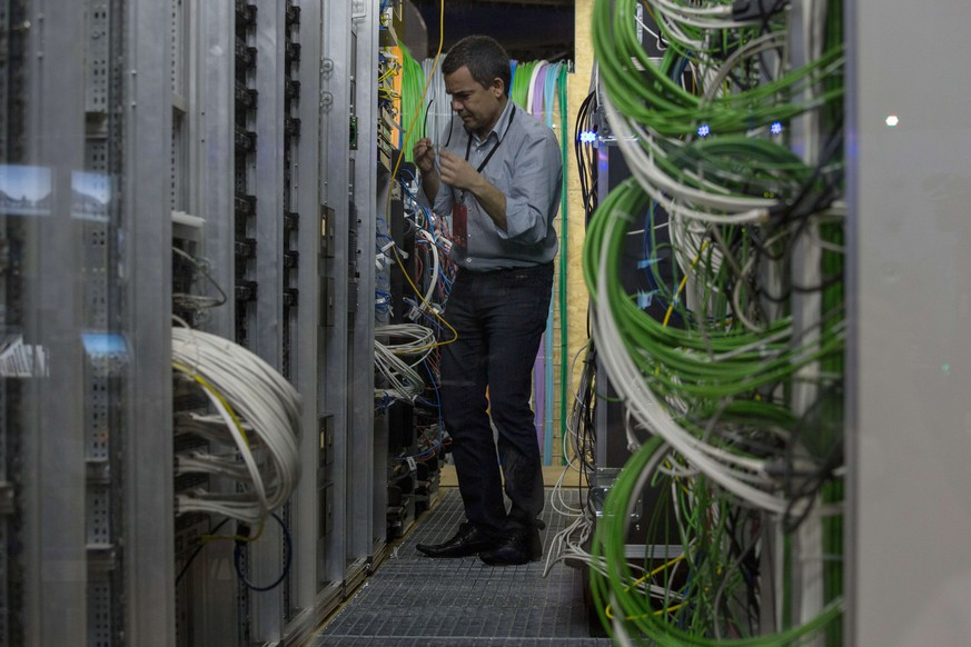 A technician work on the servers at the  master control room at the International Broadcast Centre (IBC) of the 2014 FIFA World Cup in Rio de Janeiro, Brazil, just 10 days before the event, on June 2, 2014. AFP PHOTO / YASUYOSHI CHIBA