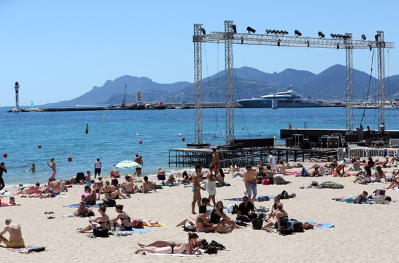 epa08402945 (20/20) (FILE) People enjoy the sun and the sea on the beach next to the giant screen of the Cinema de la Plage, the Festival's outdoors theatre, ahead of the 66th annual Cannes Film Festival, in Cannes, France, 13 May 2013 (reissued XX May 2020). The 73rd Cannes Film Festival was planned from 12 to 23 May 2020, before the new coronavirus (Covid-19) has spread to nearly every country in the world. A cancellation of the Cannes Film Festival 2020 is not on the agenda and organizers consider various options to hold the event under a different format, before the end of the year. Every year, Cannes puts on its red carpet, movie stars gather for the iconic climbing of the steps, tourists and festival-goers roam the Croisette boulevard, the camera flashes crackle. In May 2020, the atmosphere will be radically different. *** Local Caption *** 50827288  EPA/SEBASTIEN NOGIER *** Local Caption *** 50827288