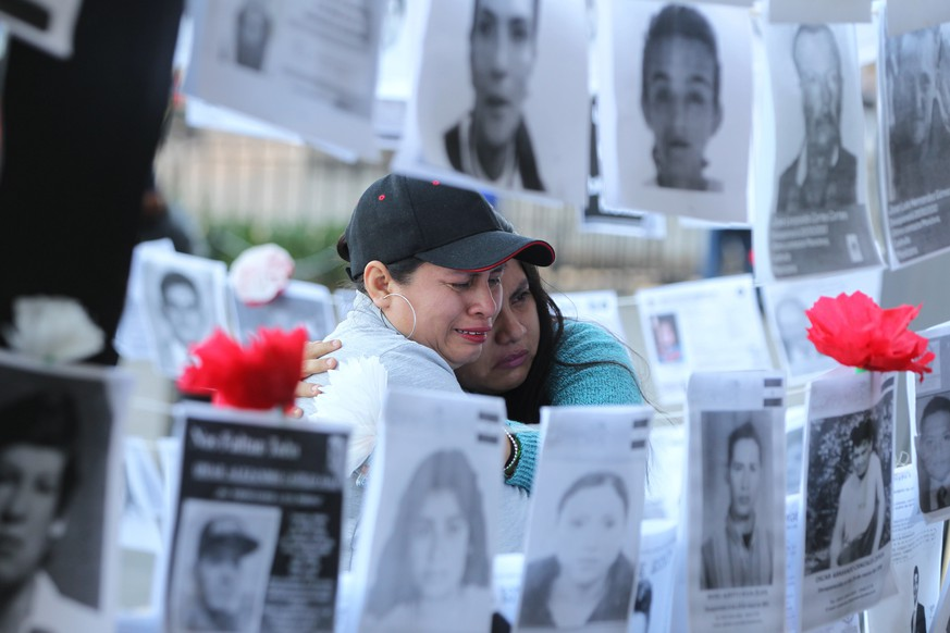 epaselect epa07804852 Women cry while looking at pictures of missing people during a demonstration in front of the National Palace, in Mexico City, Mexico, 30 August 2019. Relatives of missing people also plan to deliver 80.000 signings to demand to the Government better search protocols. At the same time Mexico's President Andres Manuel Lopez Obrador informed that authorities found 4974 bodies in 3024 clandestine graves between 2006 and mid-August 2019.  EPA/Mario Guzmán