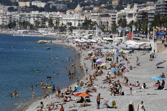 epa08536601 People enjoy the sun and the sea on a beach in Nice, southern France, 09 July 2020. Temperatures reached up to 30 degrees Celsius in Nice.  EPA/SEBASTIEN NOGIER