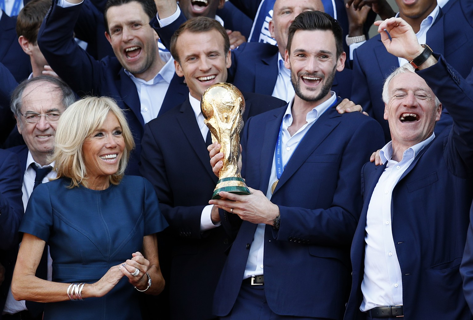 French President Emmanuel Macron, second left, his wife Brigitte, team captain Hugo Lloris holding the cup, while head coach Didier Deschamps, right, gestures at the presidential Elysee Palace after the parade down the Champs-Elysees, where tens of thousands thronged after the team's 4-2 victory over Croatia at the Monday, July 16, 2018 in Paris. (AP Photo/Francois Mori)