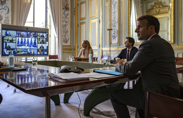epa08379773 French President Emmanuel Macron (R) attends a video conference call with members of the European Council at the Elysee Palace in Paris, France, 23 April 2020. Countries around the world are taking increased measures to stem the widespread of the SARS-CoV-2 coronavirus which causes the COVID-19 disease.  EPA/IAN LANGSDON / POOL