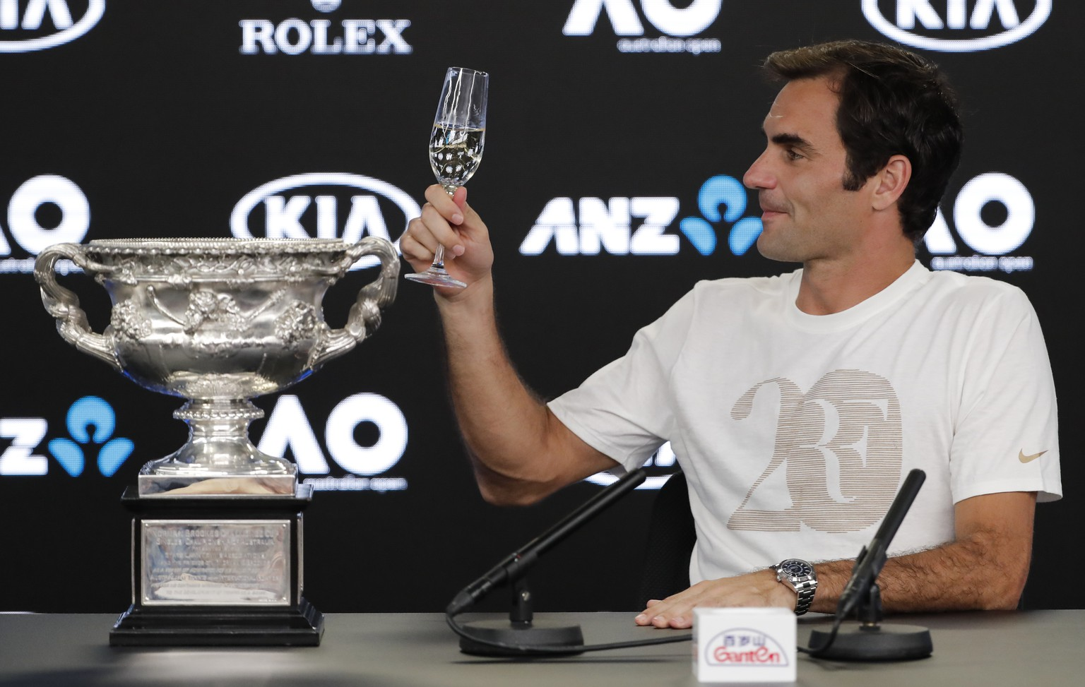 Switzerland's Roger Federer gestures with his glass of champagne at a press conference after defeating Croatia's Marin Cilic in the men's singles final at the Australian Open tennis championships in Melbourne, Australia, Monday, Jan. 29, 2018. (AP Photo/Vincent Thian)