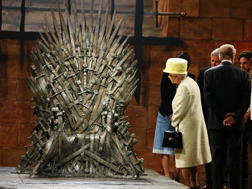 Britain's Queen Elizabeth looks at the Iron Throne as she meets members of the cast on the set of the television series Game of Thrones in the Titanic Quarter of Belfast, Northern Ireland in this file photo from June 24, 2014. HBO's medieval thriller led all nominees with 19 as the 2014 Emmy nominations were announced July 10, 2014. REUTERS/Phil Noble/Files (NORTHERN IRELAND - Tags: ENTERTAINMENT ROYALS) - RTR3VIH8