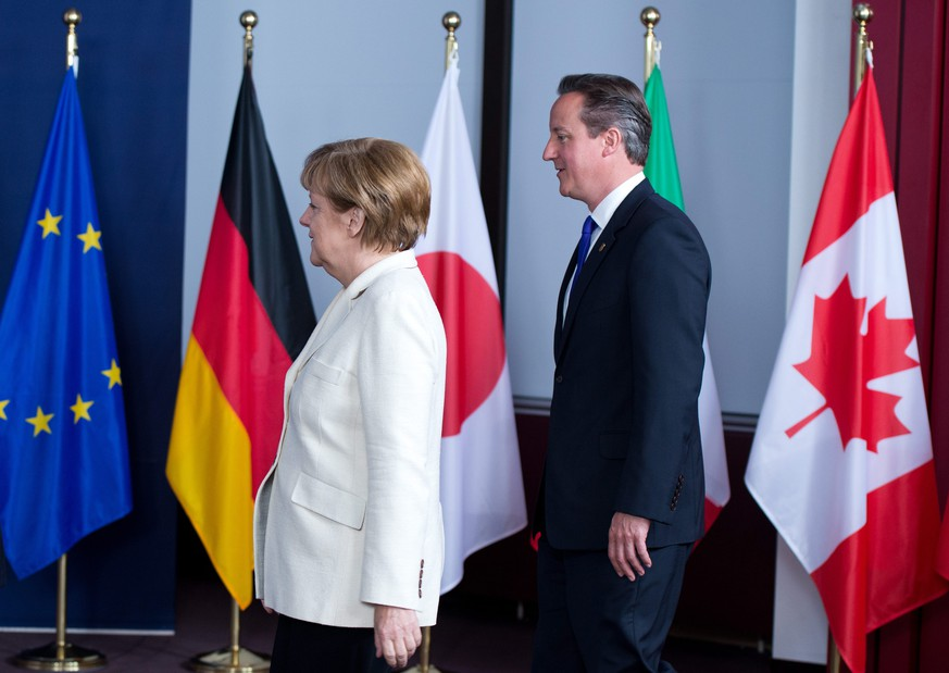epa04240485 German Chancellor Angela Merkel (L) and British Prime Minister David Cameron arrive for a family photo during the second day of the G7 Summit, at the EU Council headquarters in Brussels, Belgium, 05 June 2014. The Brussels G7 Summit will discuss the situation in Ukraine and the relations with Russia as well as other foreign policy issues, the global economy, energy, climate change and development.  EPA/BERND VON JUTRCZENKA