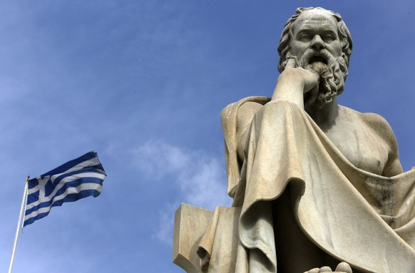 A Greek flag flutters by a statue of ancient Greek philosopher Socrates in central Athens March 18, 2015. Greek Prime Minister Alexis Tsipras on Wednesday hit back at reported criticism from European partners on a bill legislating food stamps and free electricity to the poor, saying his government will not be scared into complying with lenders.REUTERS/Yannis Behrakis (GREECE - Tags: POLITICS BUSINESS) - RTR4TVA5