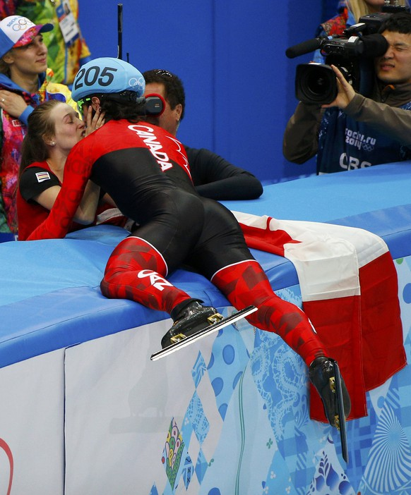 Canada's Charles Hamelin kisses his girlfriend and compatriot speed skater Marianne St-Gelais after winning the men's 1,500 metres short track speed skating race finals at the Iceberg Skating Palace during the 2014 Sochi Winter Olympics February 10, 2014.   REUTERS/Brian Snyder (RUSSIA  - Tags: OLYMPICS SPORT SPEED SKATING)