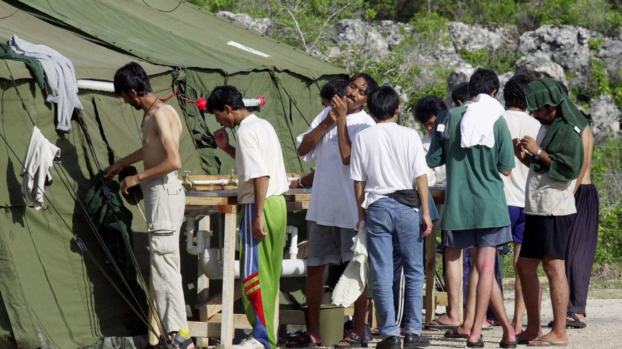 FILE - In this Sept. 21, 2001, file photo, men shave, brush their teeth and prepare for the day at a refugee camp on the Island of Nauru.  The United States and Australia are close to announcing a deal in which the U.S. would resettle hundreds of asylum seekers banished by Australia to Pacific island camps, a newspaper reported on Friday, Nov. 11, 2016.  The U.S. had agreed to accept up to 1,800 refugees held for up to three years at Australia's expense in camps on the impoverished island nations of Nauru and Papua New Guinea, The Australian newspaper reported.  (AP Photo/Rick Rycroft, File)