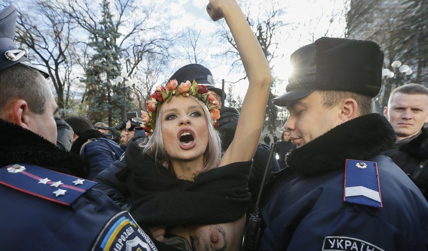 epa05021508 Ukrainian policemen arrest an activist of the women's Movement FEMEN during their topless protest 'Stop Homophobia' in front of Parliament building in Kiev, Ukraine, 12 November 2015. The activists demands the Ukrainian parliamentarians to stop the discrimination of citizens' rights by sexual orientation immediately, and to amend the Labor Code of Ukraine, in order to ensure the harmonization of Ukrainian legislation in the field of prevention and counteraction of discrimination with EU law.  EPA/SERGEY DOLZHENKO