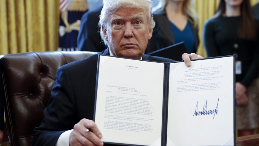 epa05747184 US President Donald Trump displays one of five executive orders he signed related to the oil pipeline industry in the oval office of the White House in Washington, DC, USA, 24 January 2017. US President Trump on 24 January 2017 signed an executive order that allows the disputed Dakota Access and Keystone XL pipelines, under the precondition that US-American steel was used. Former president Obama's administration in 2015 halted the controversial Keystopne XL project.  EPA/SHAWN THEW
