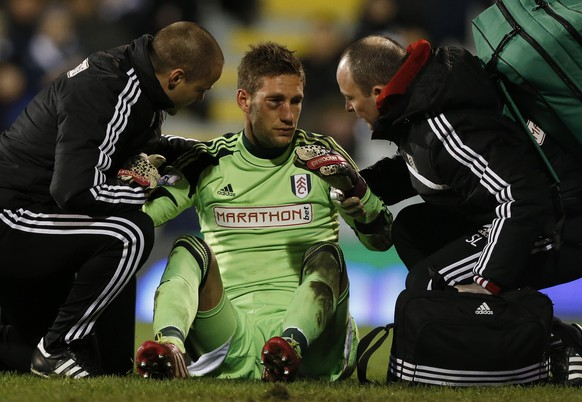 Fulham's goalkeeper Maarten Stekelenburg's eye is looked at after a crash with Liverpool's Luis Suarez during their English Premier League soccer match at Craven Cottage, London, Wednesday, Feb. 12, 2014. (AP Photo/Sang Tan)