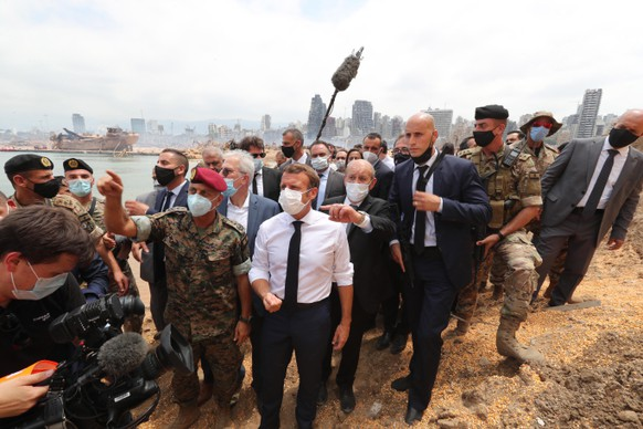 epa08587498 A handout photo made available by the Lebanese government official photographer Dalati and Nohra showing French President Emmanuel Macron (C) visiting the devastated site of the explosion at the port of Beirut, Lebanon, 06 August 2020. Macron arrived to Lebanon to show support after a massive explosion on 04 August in which at least 137 people were killed, and more than 5,000 injured in what believed to have been caused by an estimated 2,750 of ammonium nitrate stored in a warehouse.  EPA/DALATI NOHRA HANDOUT  HANDOUT EDITORIAL USE ONLY/NO SALES