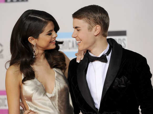 FILE - In this Nov. 20, 2011, file photo, Selena Gomez, left, and Justin Bieber arrive at the 39th Annual American Music Awards in Los Angeles. Hackers briefly took control of Gomez's Instagram account on Aug. 28, 2017, and posted nude photos of Bieber. (AP Photo/Chris Pizzello, File)